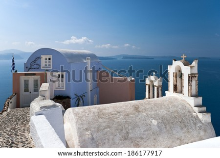 Santorini view with house and bell-towers over sea water - stock photo
