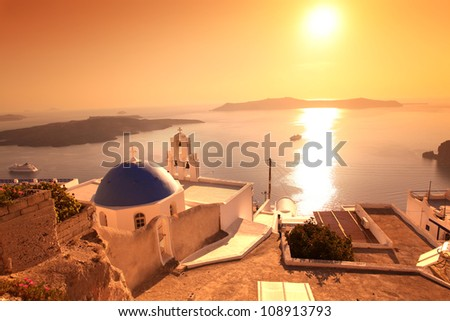 Santorini with sunset over Church in Fira town, Greece - stock photo