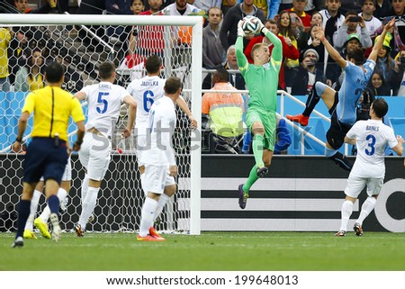 SAO PAULO, BRAZIL - June 19, 2014: Jose Gimenez of Uruguay and Joe Hart of England compete for the ball during the game between Uruguay and England at Arena Corinthians. No Use in Brazil. - stock photo