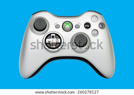 SAO PAULO, BRAZIL - MAR 13, 2014: The wireless gamepad for the Xbox 360, a home video game console produced by Microsoft, isolated on light blue background. - stock photo