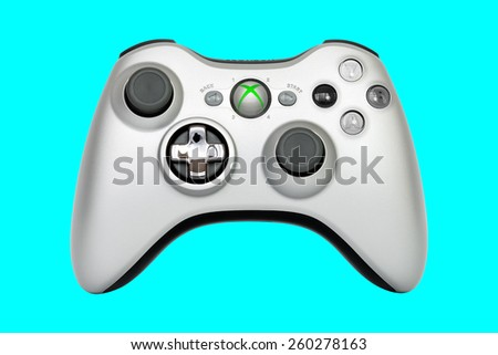 SAO PAULO, BRAZIL - MAR 13, 2014: The wireless gamepad for the Xbox 360, a home video game console produced by Microsoft, isolated on blue emerald background. - stock photo