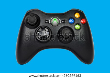 SAO PAULO, BRAZIL - MAR 13, 2014: The wireless gamepad for the Xbox 360, a home video game console produced by Microsoft, isolated on blue background. - stock photo