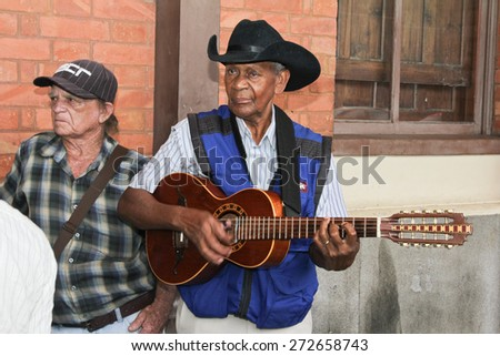 SAO PAULO, BRAZIL - MARCH 8, 2015: An unidentified group of men playing guitar and singing country musics in front of Luz Station on Sao Paulo Brazil. - stock photo