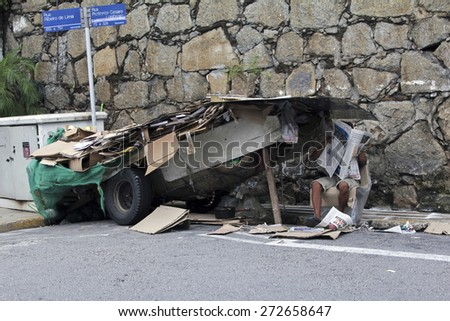 SAO PAULO, BRAZIL - MARCH 8, 2015: An unidentified recycling paper collector with his hand made car in the streets of Sao Paulo Brazil. - stock photo