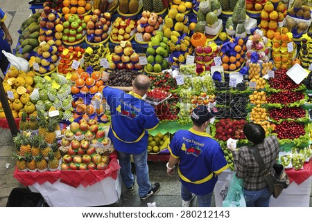 SAO PAULO/BRAZIL - MAY 9: An unidentified vendor at a fruit stand in Central Market of Sao Paulo. This landmark is a famous destination for tourists and locals. - stock photo