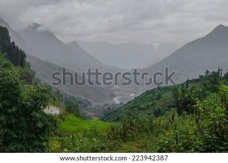 Sapa, Vietnam. Green fields and black and white mountains. - stock photo