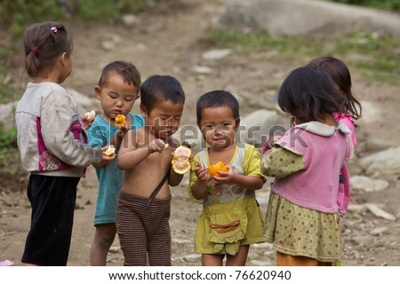 SAPA, VIETNAM - NOVEMBER 21: Six unidentified Vietnamese children play and eat in Sapa, Vietnam on November 21, 2010. Vietnam's 2011 population is 90,549,390 with 25% of the population age 14 and under - stock photo