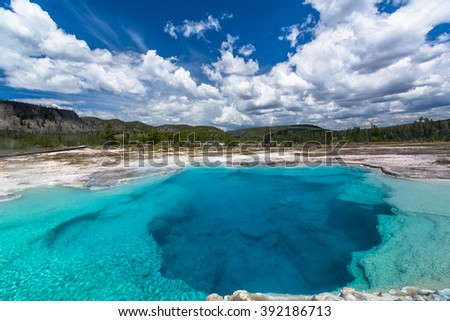 Sapphire Pool. Landscape of thermal area with clouds, thermal pool, trees, and mountain, Yellowstone National Park, USA.  Yellowstone is known as an actively volcanic activity area. - stock photo