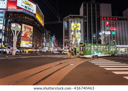 SAPPORO, HOKKAIDO, JAPAN - APRIL 24, 2016: City tram at Susukino intersection at night. Susukino is one of most popular tourist night destinations in Sapporo. - stock photo