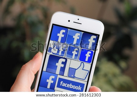 SARAJEVO , BOSNIA AND HERZEGOVINA - APRIL 22 , 2015: Woman watch Facebook icons on Apple iPhone 6. Facebook is largest and most popular social networking site in the world. - stock photo