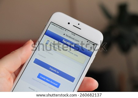 SARAJEVO , BOSNIA AND HERZEGOVINA - MARCH 14, 2015: Woman trying to login to Facebook using Apple iPhone 6. Facebook is largest and most popular social networking site in the world. - stock photo