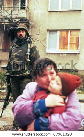 SARAJEVO, BOSNIA - MAR 18: Italian army troops, in Bosnia as part of the United Nations' UNPROFOR, watch over a refugee family in Sarajevo, Bosnia, on Monday, March 18, 1996. - stock photo