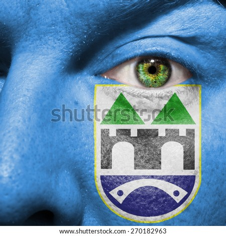 Sarajevo flag painted on a man's face to support his city Sarajevo - stock photo