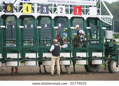 SARATOGA SPRINGS, NY- AUGUST 23: Assistant Starters are loading horses into the gate for the start of the 4th race at Saratoga Race Track, August 23, 2009 in Saratoga Springs, NY. - stock photo