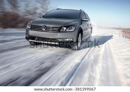 Saratov, Russia - January 26, 2014: Gray modern car Volkswagen Passat Alltrack drive speed on road at winter daytime - stock photo
