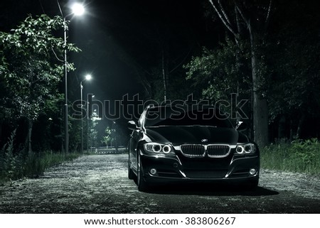 Saratov, Russia - June 12, 2015: Black car BMW E90 stay in darkness forest at night - stock photo