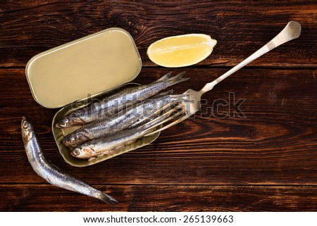 Sardines on old wooden textured background with lemon piece. Culinary healthy fish eating. - stock photo