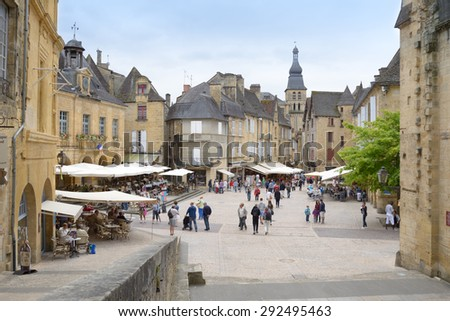 SARLAT, FRANCE - JUNE 28, 2013: Tourist walking in the historic center of old city. Since 2002, the old city of Sarlat included in UNESCO Tentative List - stock photo