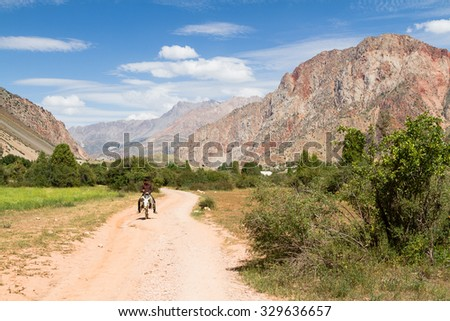 SARYTAG, TAJIKISTAN - AUGUST 2: Mountain Landscape of Fan Mountains in summer, Tajikistan, Central Asia on August 2, 2015. Donkey is a popular animal to move around on and carry loads and tourists. - stock photo