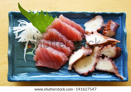 Sashimi is sliced raw fish, a traditional Japanese dish. This is tuna (maguro) and octopus (tako) with a leaf of Shiso and a little radish. - stock photo