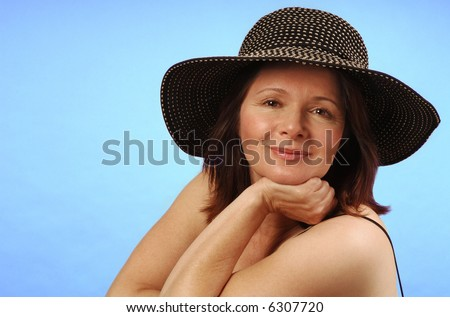 Sassy lady in a broad-brimmed sun hat against a plain background - stock photo