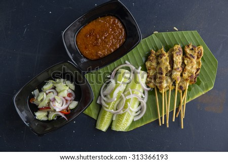Satay Thai yellow pork stick with Thai cucumber and sauces served on banana leaf - stock photo