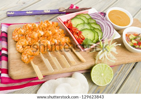 Sate Goong - Thai prawn satays served with cucumber and onion relish and peanut sauce. Side dish of cucumber, red onions and chilies. Lime and prawn crackers on foreground. - stock photo
