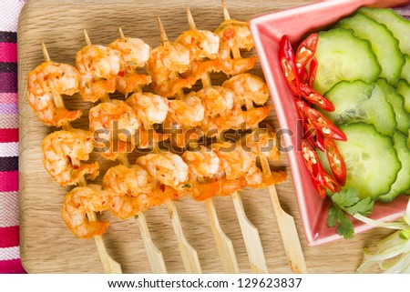 Sate Goong - Thai prawn satays served with cucumber, red onions and chilies. - stock photo