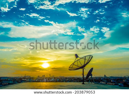 satelite dishes with sunset and city background - stock photo