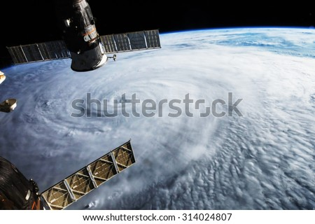 Satellite above hurricane on earth. Some graphics are provided by NASA. - stock photo