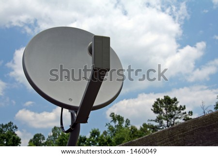 Satellite dish and cloudy blue sky background - stock photo