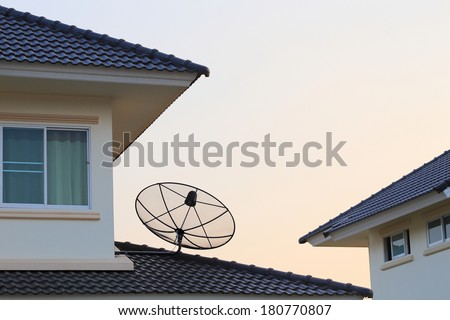 Satellite dish and TV antennas on the house roof - stock photo