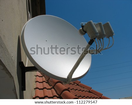 Satellite dish antenna over blue sky background - stock photo