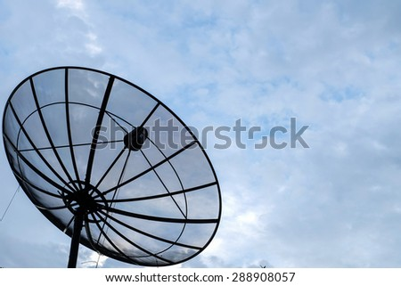 Satellite dish on cloudy sky background - stock photo