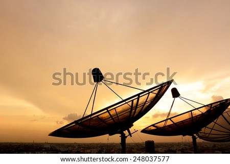 Satellite dish silhouette on twilight sky background - stock photo