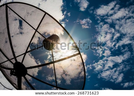 Satellite dishes communication technology network with sun and white cloud in background - stock photo