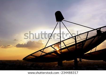 Satellite dishes on twilight sky background - stock photo