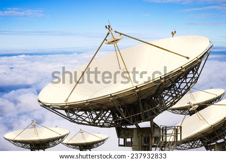 Satellite dishes over the white clouds and blue sky - stock photo