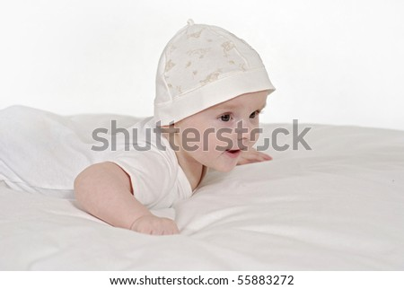 satisfied baby being in the white hat on the belly - stock photo