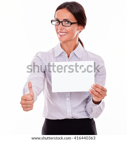 Satisfied brunette businesswoman, wearing her hair tied back and a button down shirt, holding a blank signboard with one hand and a thumb up gesture with her right hand on a white background - stock photo