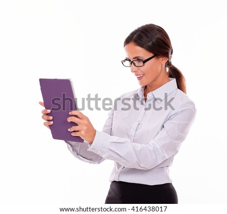 Satisfied brunette businesswoman with glasses looking at a tablet, wearing her straight hair tied back and a button down shirt, with the tablet in both hands, on a white background - stock photo