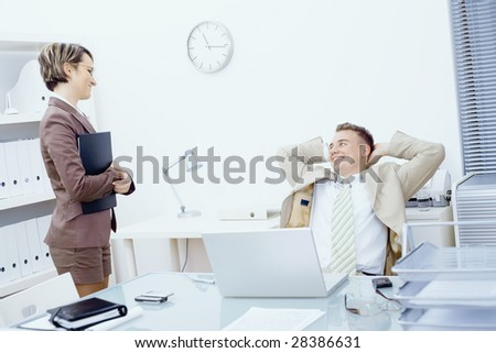 Satisfied businessman sitting at desk in office, smiling and looking up to his secretary. - stock photo