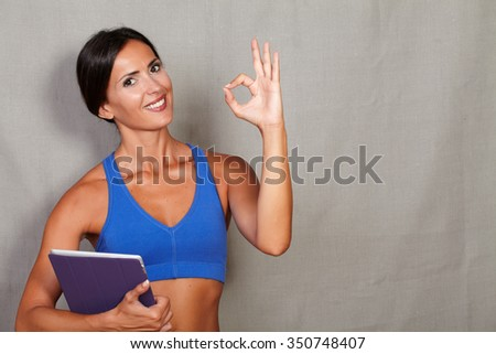 Satisfied fitness lady showing ok sign and carrying tablet against grey texture background - stock photo