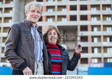 Satisfied loving senior couple with house key in hand, copyspace  - stock photo