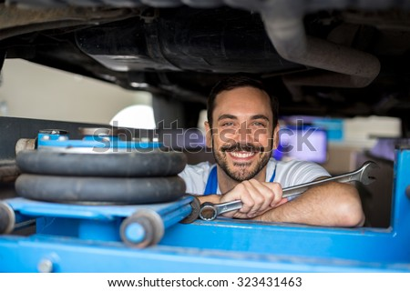 Satisfied male mechanic under car - stock photo
