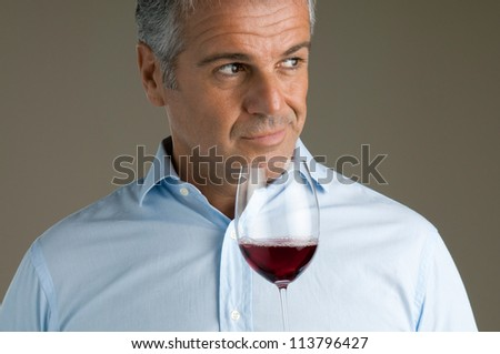 Satisfied mature sommelier smell at a glass of a red wine - stock photo