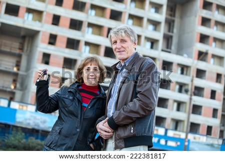 Satisfied old age couple showing house keys standing against building under construction - stock photo