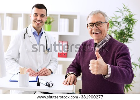 Satisfied old patient with success young doctor in office - stock photo