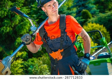 Satisfied Professional Gardener with Shoulder Lawn Mower. Landscaping Business. - stock photo