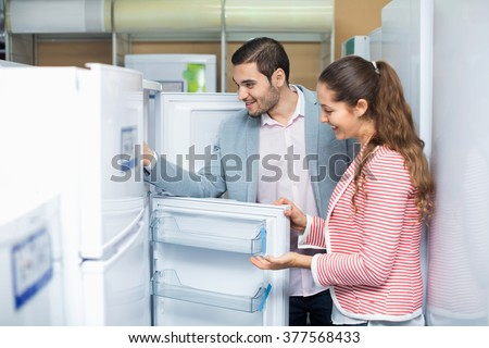 Satisfied smiling couple looking at large fridges in domestic appliances section - stock photo